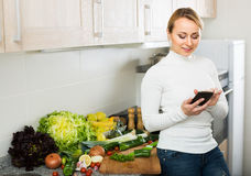 Housewife with phone at home kitchen Royalty Free Stock Photo