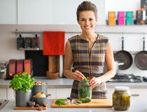 Housewife pickling cucumbers in kitchen Stock Photography