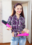 Housewife with pink dustpan and brush Stock Images