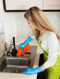 Housewife pouring detergent into  sink Stock Photo