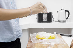 Housewife pouring flour for pie dough Stock Photography