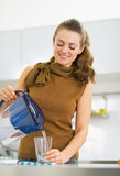 Housewife pouring water into glass from water filter pitcher. Happy young housewife pouring water into glass from water filter pitcher Royalty Free Stock Photography