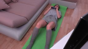 Housewife practicing fitness lessons on TV. In room stock video