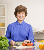 Housewife preparing salad in kitchen for dinner Royalty Free Stock Photo