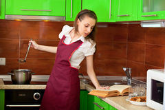 Housewife is preparing soup with book Royalty Free Stock Photo