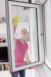 Housewife with protective glove washing the window glass Royalty Free Stock Photography