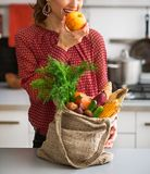 Young housewife with purchases from local market eating apple Stock Photo