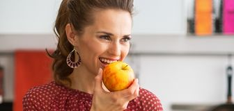 Young housewife with purchases from local market eating apple Stock Images