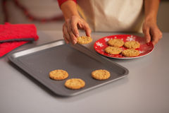 Housewife putting christmas cookies from pan to plate Stock Images