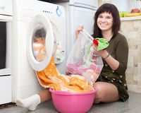 Housewife putting clothes into washing machine Royalty Free Stock Photos