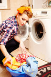 Housewife putting the laundry into the washing machine Stock Photos