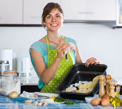 Housewife putting pieces of white fish in tray Royalty Free Stock Photography
