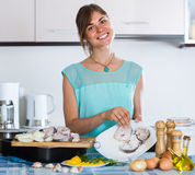 Housewife putting pieces of white fish in tray Stock Image