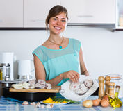 Housewife putting pieces of white fish in tray Stock Photos