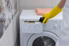 Housewife putting softener into a washing machine Stock Photos