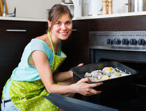 Housewife putting tray with fish in oven Royalty Free Stock Images