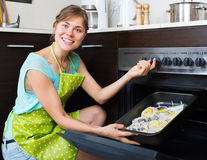 Housewife putting tray with fish in oven Royalty Free Stock Image