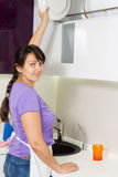 Housewife reaching for a plate in the kitchen Stock Photos