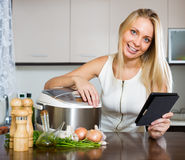 Housewife reading ereader and cooking with multicooker Stock Images