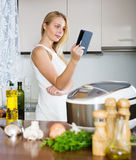 Housewife reading ereader and cooking with multicooker Stock Photography