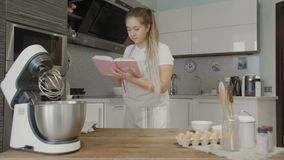 Housewife reading recipe in cookery book in the kitchen. 4K stock video footage