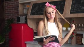 Housewife Reads Cookery Book. Neat and attractive housewife reading cookery book, blond pretty woman in white top and red checked apron learning a new recipe in stock video