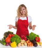 Housewife with red apron presenting fresh vegetables Stock Images