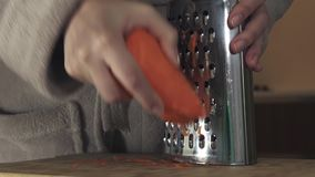 Housewife refines grated carrots in kitchen slow motion stock footage video stock video footage