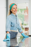 Housewife relies on a counter top. Happy housewife with blue band on head relies on a shiny counter top royalty free stock images