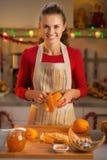Housewife removing orange peel in kitchen Stock Photo