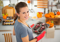 Housewife removing from oven tray with Halloween biscuits Stock Photo