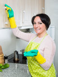Housewife removing spots from cupboards in kitchen Royalty Free Stock Images