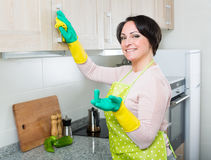 Housewife removing spots from cupboards in kitchen Royalty Free Stock Photography