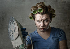 Housewife sad bored and stressed holding iron angry and frustrated. Young attractive woman or housewife sad bored and stressed holding iron angry and frustrated royalty free stock photography