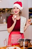 Housewife in Santa Claus hat cooking Christmas dinner royalty free stock images