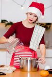 Housewife in Santa Claus hat cooking Christmas dinner stock images