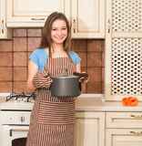 Housewife with saucepan and heat insulation gloves. Young woman Royalty Free Stock Photos