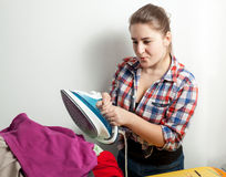 Housewife in shirt ironing clothes Royalty Free Stock Photography