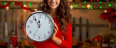 Housewife showing clock in christmas decorated kitch Stock Photography