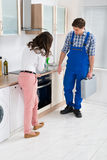 Housewife Showing Damaged Oven To Worker Stock Photo
