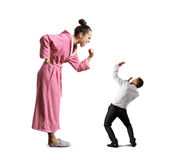 Housewife showing fist to man. Angry screaming housewife showing fist to small scared man. isolated on white background Royalty Free Stock Images
