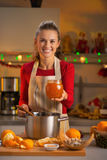 Housewife showing homemade orange jam. Portrait of smiling young housewife showing homemade orange jam Stock Image