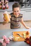 Housewife showing jar with homemade apple jam Stock Photo