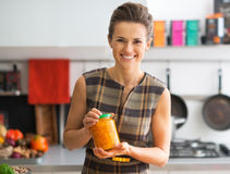 Housewife showing jar of pickled pumpkin Stock Image