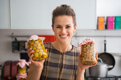 Housewife showing jars with homemade compote Royalty Free Stock Photography