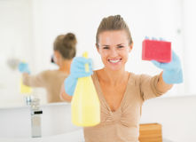 Housewife showing spray bottle and sponge Stock Photography