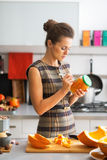 Housewife signing jar of pickled pumpkin Royalty Free Stock Images