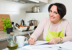 Housewife signing papers in kitchen Stock Image