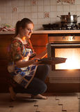 Housewife sitting next to oven and holding pan near hot oven Royalty Free Stock Photo