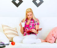 Housewife sitting on sofa and reading book Royalty Free Stock Photo